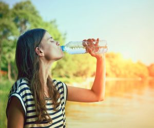 young woman drinking bottled water near a lake