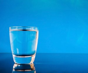 Glass of water on a reflective surface